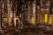Cambodian girl shows apsera position next to ancient Angkor Kdei Temple. Apsara's are all glowing gold.