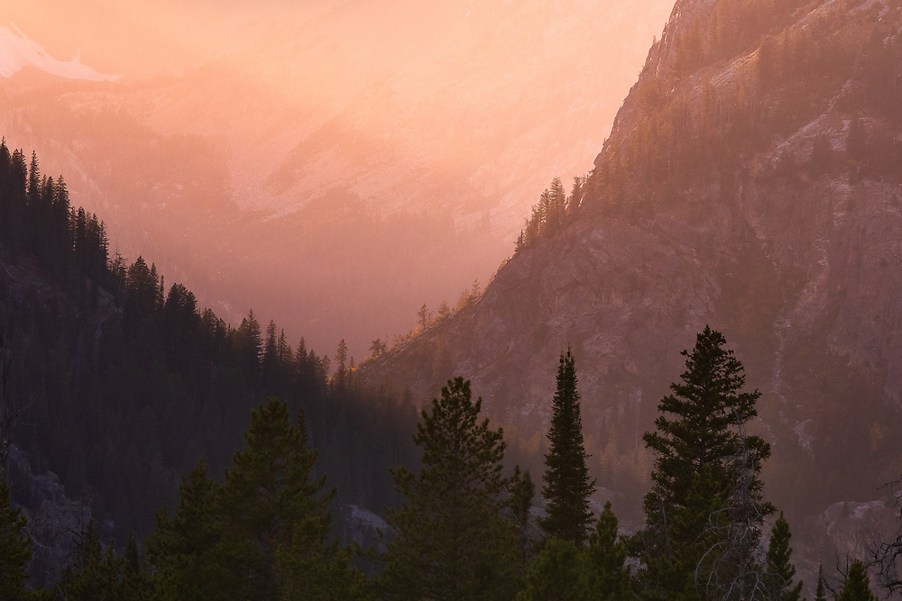 Late evening sun light washes over the base of the Grand Tetons setting aglow the distant hazy air surrounding the low lying valley composed of rock and pine.