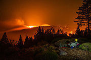 HEALDSBURG, CA - OCTOBER 29: 37 year old Alex DeLeon with Engine 342 of the Lake Tahoe Basin Management Unit of the U.S. Forest Service watches the Kincade fire burn on a ridge between Lake and Sonoma Counties, as he stands watch at a home above Knights Valley east of Healdsburg, California on October 29, 2019. A light painting technique was used during a long exposure image capture to include Mr. DeLeon in the image. (Photo by Philip Pacheco/AFP)