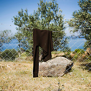 A shirt left on the road between Mantamado and Mytilini. Most refugees land on the northern shores of the island and they walk for nine hours either to Mytilini port or to Moria  First Reception Centre..Everyday hundreds of refugees, mainly from Syria and Afghanistan, are crossing in small overcrowded inflatable boats the 6 mile channel from the Turkish coast to the island of Lesbos in Greece.