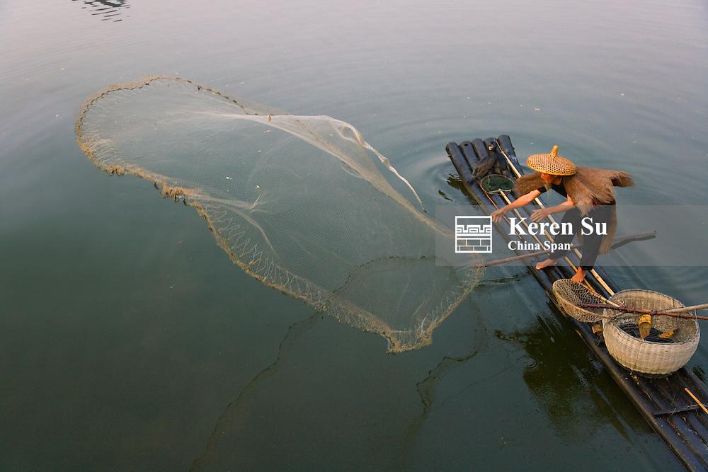 Fisherman cast fishing net from bamboo raft on the Li River, Yangshuo, Guangxi, China