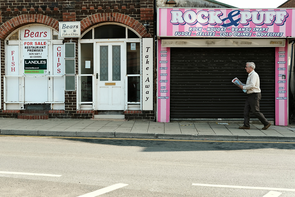 A man rushes past a closed down restaurant & rock shop on a busy hot last day of the Summer in Hunstanton Norfolk, the first summer in the UK during the COVID-19 pandemic.<br /> <br /> Photo by Jonathan J Fussell, COPYRIGHT 2020