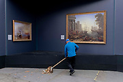 A street sweeper brushes leaves from beneath a copy of Seaport with the Embarkation of Saint Ursula by Claude Lorrain 1641, part of a temporary display of historical art placed outside the National Gallery to show passers-by what can be seen in their galleries, on 1st September 2021, in Trafalgar Square, London, England.