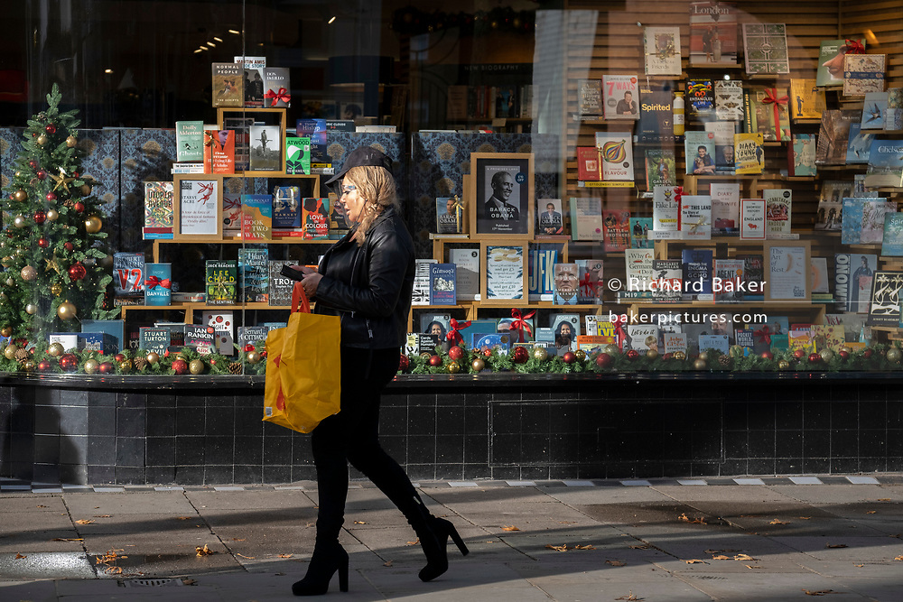 A shopper wearing a face shield walks past Christmas books stock in the window of a closed Chelsea branch of Waterstones on the King's Road during the second Coronavirus lockdow when most non-essential retailers and small businesses remain closed by order of the government, on 13th November 2020, in London, England.