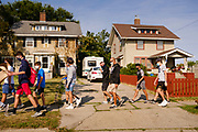 07 SEPTEMBER 2020 - DES MOINES, IOWA: About 300 Des Moines Public School (DMPS) high school athletes march through a residential neighborhood in Des Moines on their way to the Governor's Mansion Monday to protest Gov. Kim Reynolds' recent efforts to reopen schools. DMPS, the largest school district in Iowa, is suing to go to online instruction because of the COVID-19 pandemic. The Governor is trying to force the district to reopen with in person instruction. The state ruled that schools using online education can't participate in extracurricular activities, including sports. The student athletes, who all wore face masks to comply with CDC guidelines, were marching to demand the ability to participate in sports despite using online instruction.     PHOTO BY JACK KURTZ
