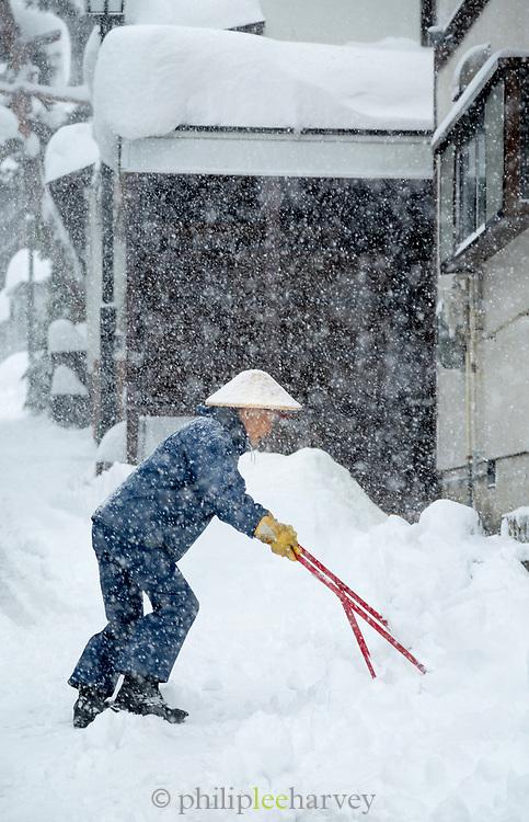 Man shoveling snow on street, Nozawaonsen, Japan