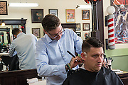 Josh Ward, owner of Bluejay's Barber Shop in Enid, Oklahoma, cuts the hair of one of his customers.