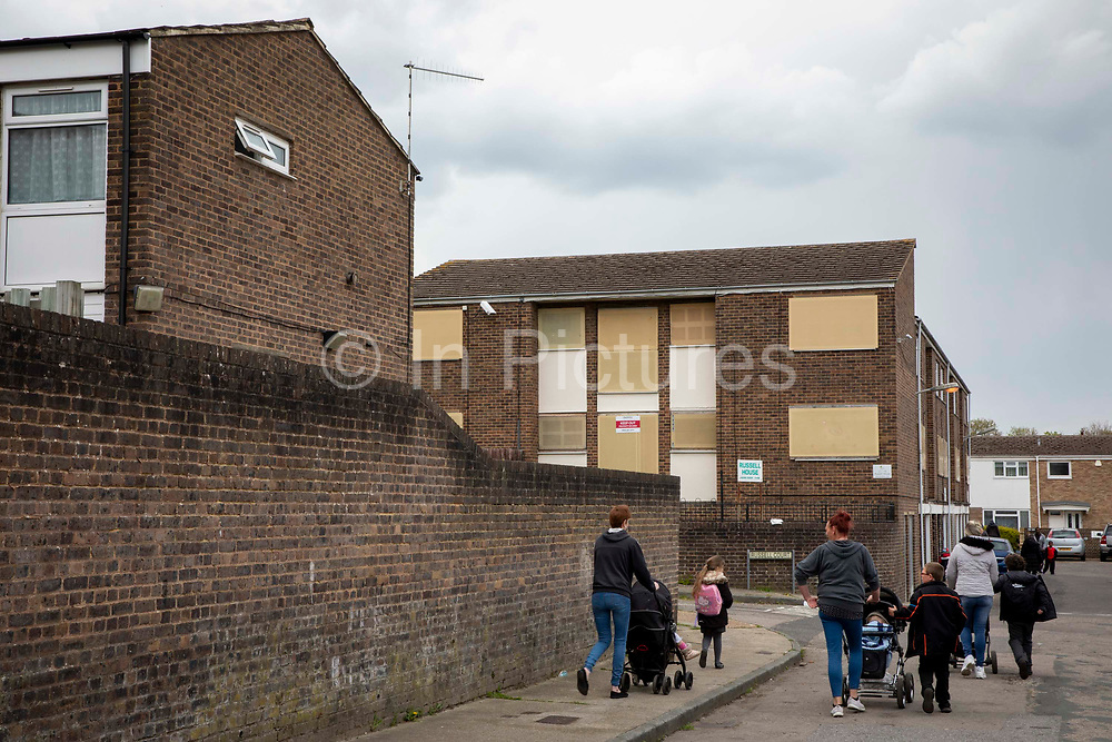 Young Familes walk home from school past the boarded up and soon to be refurbished Russell House on the 30th of April 2021 in Chatham, Kent, United Kingdom. The former housing shelter for elderly people is set to be refurbished by MHS homes and replaced with accommodation for vulnerable young people.