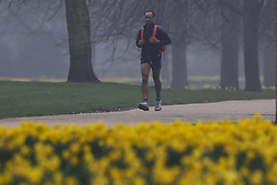 © Licensed to London News Pictures. 03/03/2021. London, UK. An early morning jogger runs through a foggy St James's Park in central London. Later Chancellor Rishi Sunak will deliver his budget to Parliament. Photo credit: Peter Macdiarmid/LNP