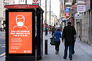 Transport for London digital advertising posters at promoting face mask wearing at bus stops along Oxford Street which is empty of shoppers as the national coronavirus lockdown three continues on 28th January 2021 in London, United Kingdom. Following the surge in cases over the Winter including a new UK variant of Covid-19, this nationwide lockdown advises all citizens to follow the message to stay at home, protect the NHS and save lives.