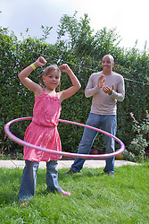 Little girl playing with a hulahoop in the garden with her father,