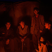 KABUL, AFGHANISTAN - NOVEMBER 14, 2012: Afghan boys sit around a fire after a long day scavenging for recyclables at a garbage dump site in the outskirts of Kabul.