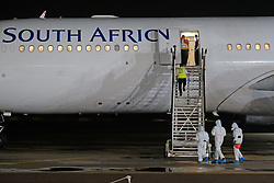PRETORIA SOUTH AFRICA - APRIL 26: South African health official board an SAA flight with a Cuban Health Brigade, consisting of 217 Cuban Health proffesionals who arrived at Waterkloof Airforce Base. on April 26, 2020 in Pretoria South Africa. Under pressure from a global pandemic. President Ramaphosa declared a 21 day national lockdown extended by another two weeks, mobilising goverment structures accross the nation to combat the rapidly spreading COVID-19 virus - the lockdown requires businesses to close and the public to stay at home during this period, unless part of approved essential services. (Photo by Dino Lloyd)