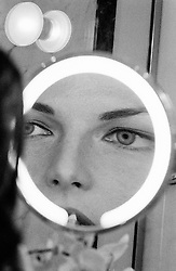 Woman looking into a magnifying mirror while putting on lipstick