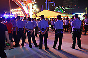 Police officers stand on watch at the carnival grounds of the Qingdao (Tsingtao) Beer Festival in Qingdao, China on 27 August, 2011. Named after the locally brewed Tsingtao Beer, one of China's most famous exports, the festival has grown from a local binge drinking feast to an internationally known festival.