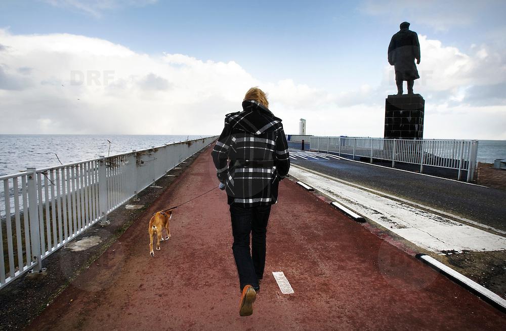 Nederland Den Oever Zurich 22 november 2008 20081122 Foto: David Rozing ..Serie afsluitdijk. De Afsluitdijk is een belangrijke waterkering en verkeersweg in Nederland. De waterkering sluit het IJsselmeer af van de Waddenzee. Hieraan ontleent de dijk zijn naam. De verkeersweg, onderdeel van Rijksweg a7, verbindt Noord-Holland met Friesland...Vrouw laat hond uit op afsluitdijk in stormachtig weer, rechts standbeeld van Cornelis Lely, gemaakt door beeldhouwer Mari Andriessen. Cornelis Lely was in 1913 minister van waterstaat en stond aan de wieg van de afsluitdijk.  deltaplan..Foto David Rozing