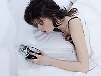 one young woman awakening late  in a white sheet bed on white background