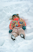 Girl age 4 making snow angels in the snow.  St Paul  Minnesota USA