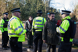 Denham, UK. 6 February, 2020. Police officers move on Sarah Green (c) and Mark Keir (r), environmental activists from Save the Colne Valley, who were walking at a snail's pace along a road in order to block a security vehicle and truck delivering fencing and other supplies to be used for works associated with the HS2 high-speed rail link close to the river Colne at Denham Ford. Works planned in the immediate vicinity include the felling of trees and the construction of a Bailey bridge, compounds and fencing, some of which in a wetland nature reserve forming part of a Site of Metropolitan Importance for Nature Conservation (SMI).