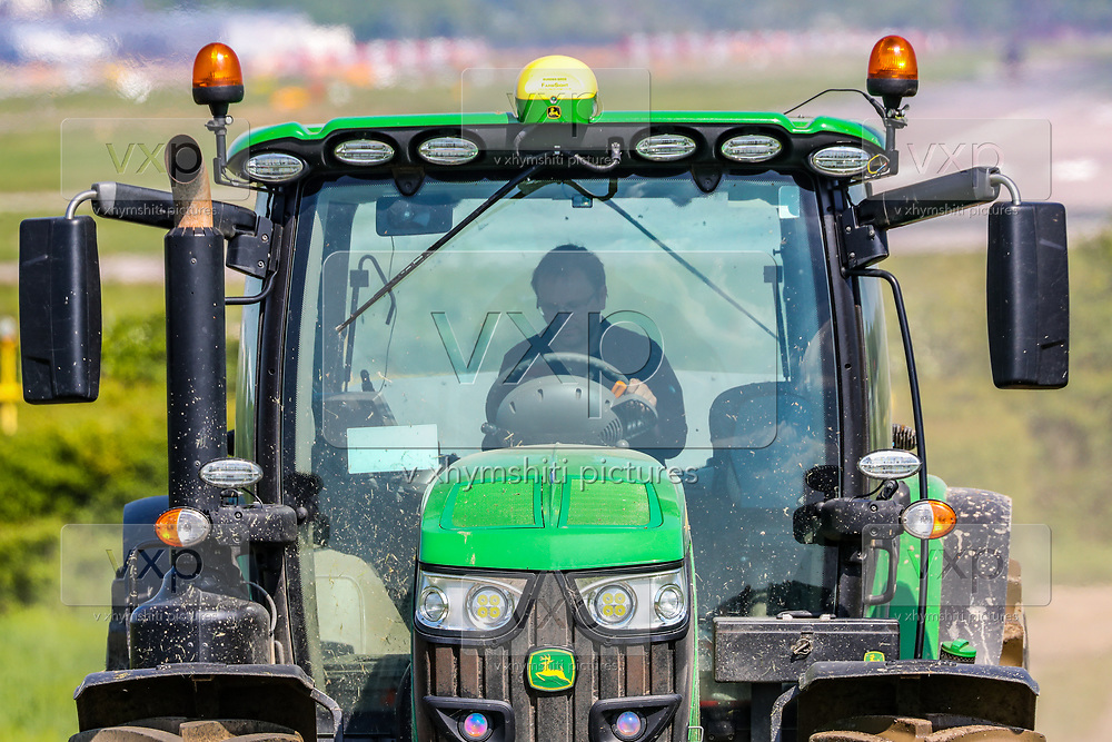 A local farmer in Charlwood Village near Gatwick airport is seen driving his tractor towards his farmland opposite airport's deserted runway as EasyJet planes were seen grounded at Gatwick Airport in Sussex due to the coronavirus pandemic outbreak in Britain, Wednesday, May 6, 2020. (Photo/ Vudi Xhymshiti)