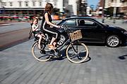 In Zeist rijdt een vrouw met een kind achterop op de fiets door het centrum terwijl ze wordt ingehaald door een auto.<br /> <br /> Cyclists in the city center of Zeist.