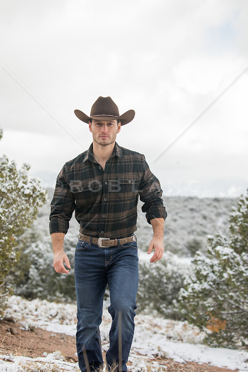 handsome rugged cowboy walking on a snow covered mountain range