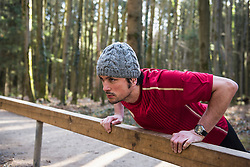 Man doing push-ups on fitness trail in forest