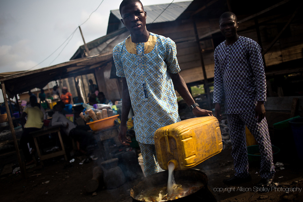 The son of a traditional medicine seller, known for a concoction that will induce miscarriage, brews a mixture in the Badia neighborhood of Lagos, Nigeria, August 30, 2013.  The craft has been in the family-- which also makes remedies for health concerns like malaria and stomach aches-- for at least three generations.