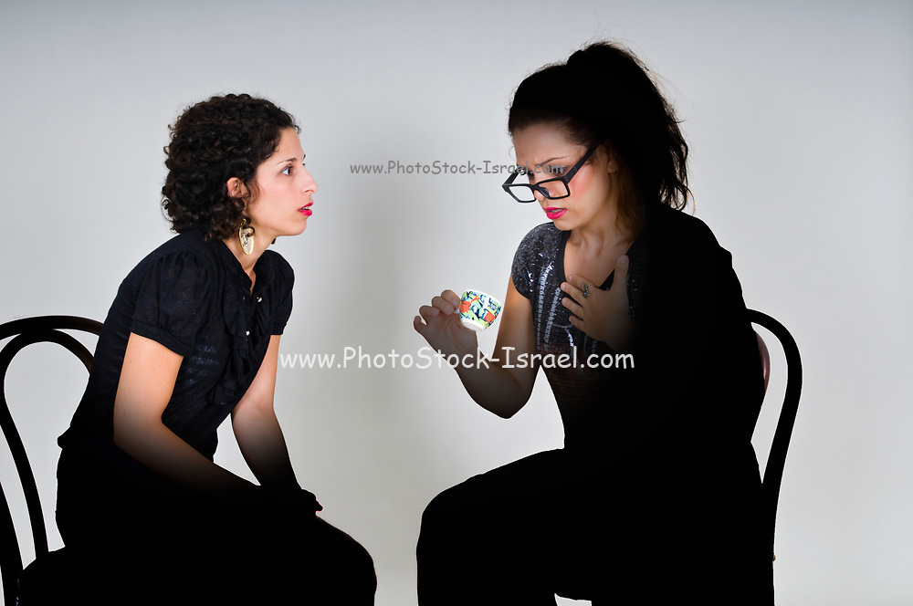 illuminated faces as a Fortune teller reads a young woman's future in a coffee cup