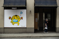 A man stands outside a closed business as artwork of author and illustrator Roger Hargreaves' 'Little Miss Sunshine' character wearing a face mask is painted on the outside of a boarded up window, in downtown Vancouver, BC, Canada on Sunday, April 19, 2020. TPhoto by Darryl Dyck/CP/ABACAPRESS.COM