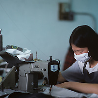 China, Hong Kong, Woman works in garment sweatshop in New Territories