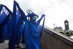 The blue rebels walk along the South Bank with fellow climate activists from the Ocean Rebellion and Extinction Rebellion during a colourful Marine Extinction March on 6 September 2020 in London, United Kingdom. The activists, who are attending a series of September Rebellion protests around the UK, are demanding environmental protections for the oceans and calling for an end to global governmental inaction to save the seas.
