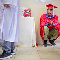 Henry Brown sits in a corner among his classmates before the New Life Learning Center graduation ceremony Friday at Lighthouse Church in Gallup.