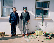 Two part-time air show commentators stand on the harbour wall at St. Peter Port, Guernsey, Channel Islands. During a break in the show's sequence of flying by an assortment of military aircraft, the two men stand in the shade on this warm summer day. Wearing headsets and microphones, the elderly gents are surrounded by broadcasting wiring and digital sound gadgets.