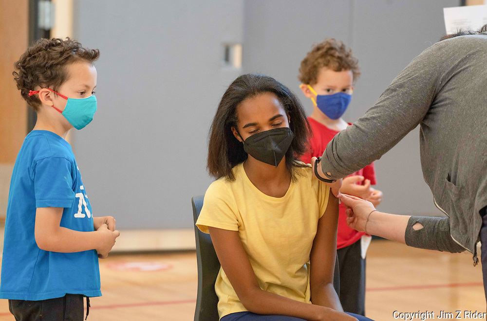 Kaya Dollery, 13, of Philadelphia, PA, receives her vaccination under the watchful eye of her brothers.