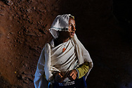 Portrait of a young Amhara boy taken inside a passage carved out of the rock in Lalibela, Ethiopia