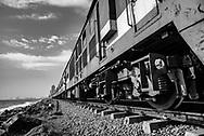 Low angle view of a passenger train traveling along the coast of Colombo, Sri Lanka.