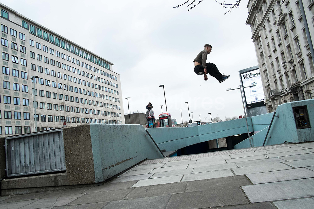 Free Runners practicing Parkour. Parkour is a holistic training discipline enabling practitionaers to get from A to B in the most effective way possible. It has developed from military training in tackling obstacle courses and the runners focus on maintaining as much momentum as possible jumping, swinging, rolling and vaulting using their urban environment for propulsion. Waterloo, London.