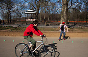 People gather to walk along the edge of The Serpentine in Hyde Park, London. This is a popular place for cycling and rollerblading.