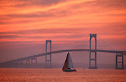 USA, Newport, RI - Alone in the bay, a sail boat crosses by the Newport Bridge and an intensely lit sunset sky.
