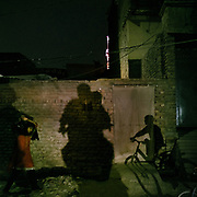 Evening activities: a girl brings back groceries, a boy on a bicycle and father and son returning on a motorcycle. In the city of Jacobabad.