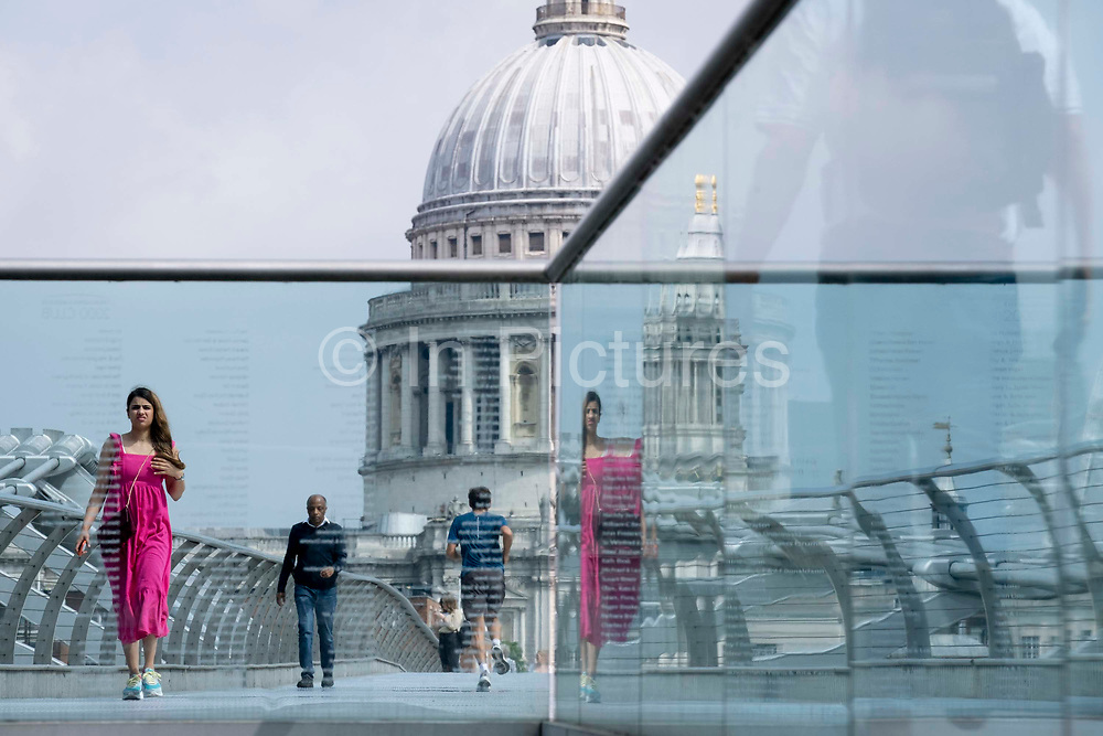With the dome of St Pauls cathedral in the distance, a woman in a crimson dress crosses the river Thames on the Millennium Bridge, on 24th June 2021, in London, England. Londons newest river crossing for 100-plus years coincided with the Millennium. It was hurriedly finished and opened to the public on 10 June 2000 when an estimated 100,000 people crossed it to discover the structure oscillated so much that it was forced to close 2 days later. Over the next 18 months designers added dampeners to stop its wobble but it already symbolised what was embarrassing and failing in British pride. Now the British Standard code of bridge loading has been updated to cover the swaying phenomenon, referred to as Synchronous Lateral Excitation.