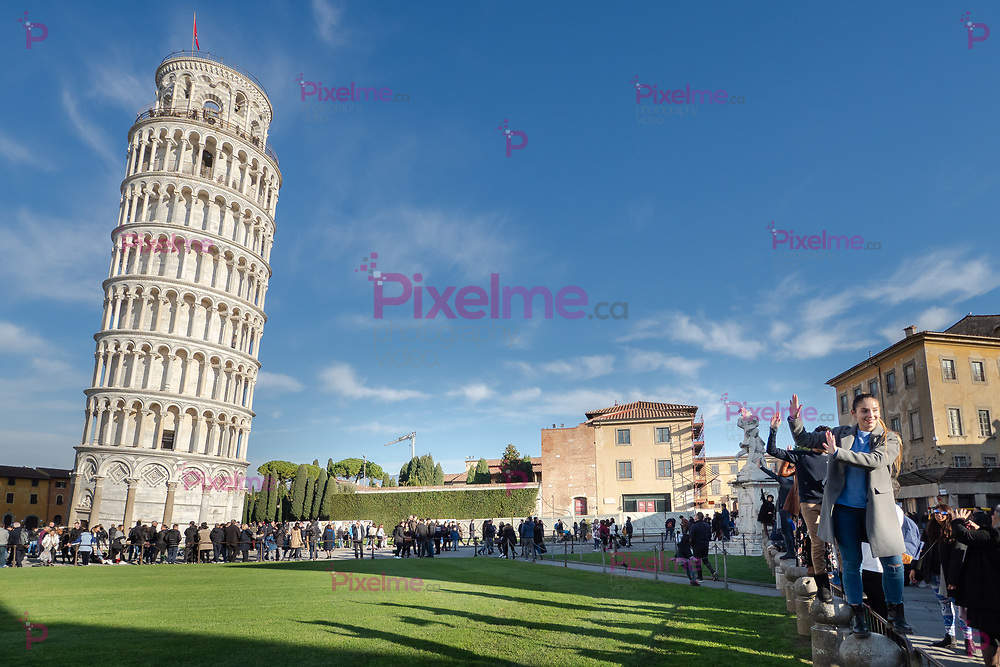 January 01, 2019 Pisa, Tuscany, Italy - Leaning Tower of Pisa and a side of the Pisa Cathedral with tourists posing as if they hold the tower on a clear day