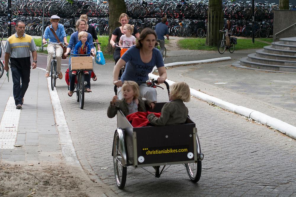 Ouders fietsen met hun kinderen over het Smakkelaarsveld in Utrecht.<br /> <br /> Parents are cycling with their children in Utrecht.