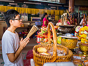 """07 AUGUST 2014 - BANGKOK, THAILAND:  A man prays at an alter at Pek Leng Keng Mangkorn Khiew Shrine. Thousands of people lined up for food distribution at the Pek Leng Keng Mangkorn Khiew Shrine in the Khlong Toei section of Bangkok Thursday. Khlong Toei is one of the poorest sections of Bangkok. The seventh month of the Chinese Lunar calendar is called """"Ghost Month"""" during which ghosts and spirits, including those of the deceased ancestors, come out from the lower realm. It is common for Chinese people to make merit during the month by burning """"hell money"""" and presenting food to the ghosts. At Chinese temples in Thailand, it is also customary to give food to the poorer people in the community.     PHOTO BY JACK KURTZ"""