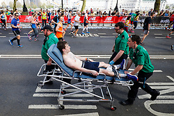 © Licensed to London News Pictures. 22/04/2018. London, UK. A runner is is carried off by stretcher during the 2018 London Marathon which is being run in unusually warm temperatures for April. This years event is being started by HRH Queen Elizabeth II. Photo credit: Tom Nicholson/LNP