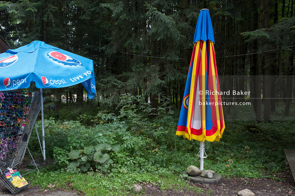 A landscape of a folded parasol standing in woods near the entrance of the Dolina Chocholowska hiking route in the Tatra National Park, on 17th September 2019, near Zakopane, Malopolska, Poland.