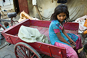A young homeless girl sits atop a cart used by her family picking up rubbish to resell. Karol Bagh, New Delhi, India.