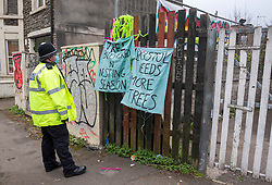 "© Licensed to London News Pictures; 01/03/2021; Bristol, UK. A police officer looks at a campaigners sign saying ""Bristol needs more trees"" after the last remaining Maple tree out of the original five that Save The M32 Maples campaigners have been fighting to save was cut down. Contractors working for the owners began cutting the base of the tree before dawn when a woman called Kate got up the tree but no one was injured. Council contractors were then called in to complete the work and police blocked off the road. The campaign wants the importance of mature trees reflected in council policy and that developers integrate their projects whilst preserving existing trees to enhance the environment and help remove pollution in what is a traffic congested area. Photo credit: Simon Chapman/LNP."