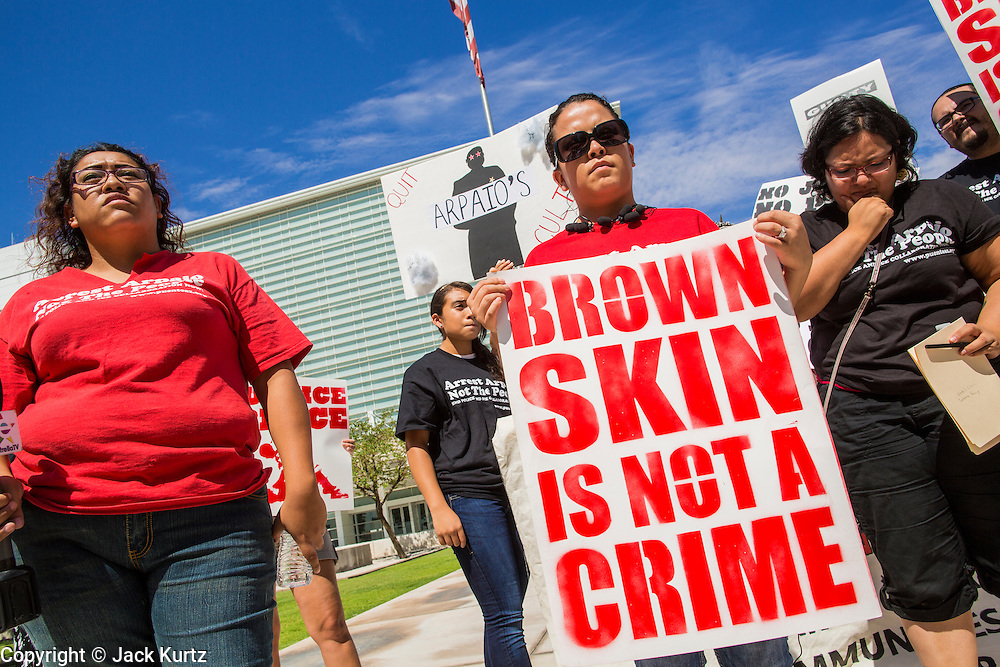 """19 JULY 2012 - PHOENIX, AZ: LETICIA RAMIREZ (left) and NATALLY CRUZ (right) both from Puente, a human rights organization, speak out against Maricopa County Sheriff Joe Arpaio in front of the US Courthouse on the first day of a class action lawsuit, Melendres v. Arpaio in Phoenix Thursday. The suit, brought by the ACLU and MALDEF in federal court against Maricopa County Sheriff Joe Arpaio, alleges a wide spread pattern of racial profiling during Arpaio's """"crime suppression sweeps"""" that targeted undocumented immigrants. U.S. District Judge Murray Snow granted the case class action status opening it up to all Latinos stopped by Maricopa County Sheriff's Office deputies during the crime sweeps. The case is being heard in Judge Snow's court.   PHOTO BY JACK KURTZ"""